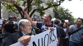 一名男子不顾伤势,在示威现场拍照。