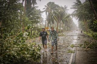 news Two people walk along a road past uprooted trees