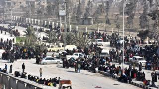 Syrian civilians arrive at a checkpoint manned by pro-government forces after leaving eastern Aleppo on 10 December 2016