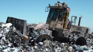 File image of a rubbish compactor at a landfill site