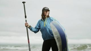 Sian Sykes with a paddleboard stood in the sea