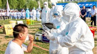 Un hombre en China con gripe es atendido por personal sanitario.