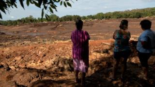 Moradores olham para área destruída pela lama, em Brumadinho