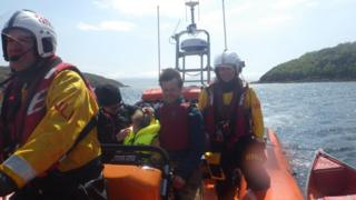 RNLI volunteers with family of kayakers