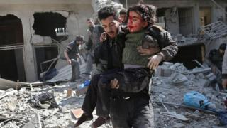 Un hombre lleva en brazos a un niño víctima de un ataque en Guta Oriental, Damasco, Siria.