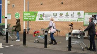 Shoppers queue using social distancing outside supermarket in England