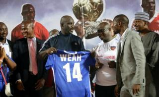 President George Weah (3-L), receives his #14 jersey from Mustapher Raji (2-R), President of the Liberia Football Association(LFA), an other officials after an international friendly match between Liberia and Nigeria, to mark the final retirement of his official #14 jersey for Liberia, at the Samuel Kanyon Doe Sports Complex in Paynesville, Liberia, 11 September 2018