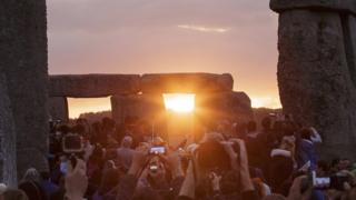 People gather at Stonehenge to experience the sun rising on the longest day of the year
