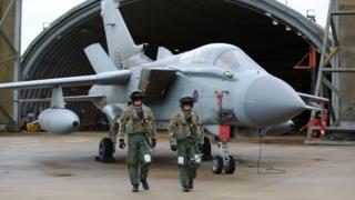 Pilots walk away from a Tornado fighter jet at RAF Marham in Norfolk, UK - 2 December 2015
