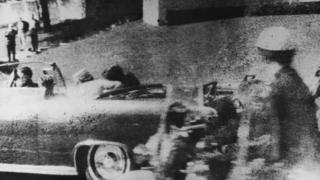 American president John F. Kennedy (1917 - 1963) is struck by an assassin's bullet as he travels through Dallas in a motorcade, 22nd November 1963.