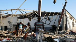 Migrants carry the remains of their belongings from among rubble at a detention centre for mainly African migrants that was hit by an airstrike in the Tajoura suburb of the Libyan capital of Tripoli, Libya July 3