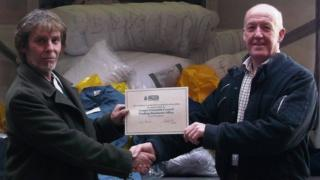 John Eden Jones from Gwynedd Council's Trading Standards Service handing over the counterfeit clothing to David Scott from the National Police Aid Convoy charity