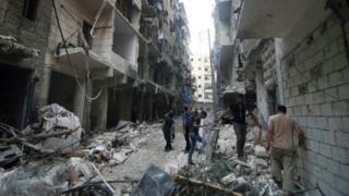 Halep'teki hasarı inceleyen Suriyeliler