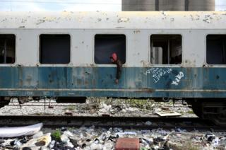 Habib from Algeria sits in an abandoned railway wagon