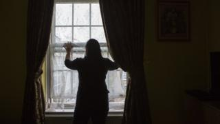 An unidentified lady stands silhouetted in front of her living room window