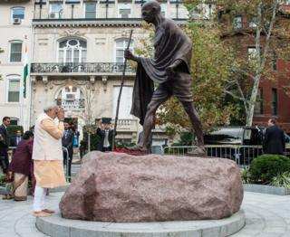Indian Prime Minister Narendra Modi pays his respects at a statue of Mahatma Gandhi in front of the Indian embassy in Washington on September 30, 2014.