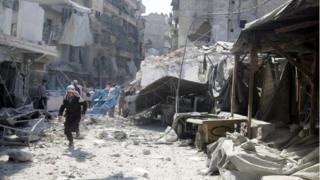 A civil defence member runs in market hit by air strikes in al-Fardous district of Aleppo