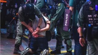 Hong Kong police detain a man in Causeway Bay, 12 June