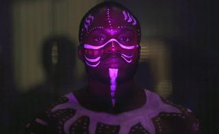 A model with white face decorations lit up by ultraviolet light during a fashion show in Santiago, Chile - Friday 24 February 2017