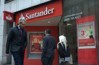 People walk past a Santander branch