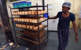 In this photograph taken on December 19, 2014 an Indian worker pulls a bread rack