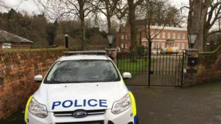 Police car parked outside the house's gates