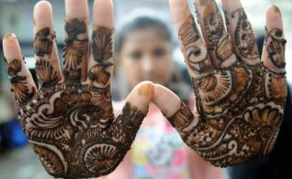 An Indian Muslim girl displays her henna decorated hands at a roadside stall ahead of the Muslim festivities of Eid al-Fitr, in Mumbai on July 28, 2014