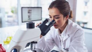 A scientist with a microscope (stock image)