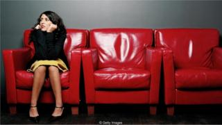 kırmızı koltukta mülakat sırasını bekleyen kadın