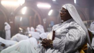 Worshippers pray during a Good Friday Lent church service at the Eternal Sacred Order of Cherubim and Seraphim Church in London