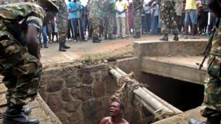 A bloodied man in a pit begs as he is surrounded by soldiers