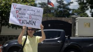 A man holds a placard reading 'Taiwan, in the Name of the Salvadorean People, I Come to Ask For Forgiveness' in front of the embassy of Taiwan in San Salvador on August 21, 2018