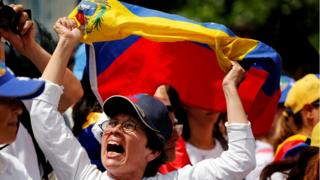 Una mujer protesta con la bandera de Venezuela entre sus manos.