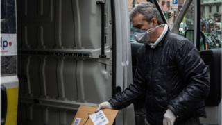 A courier, wearing a respiratory mask, handles an Amazon parcel