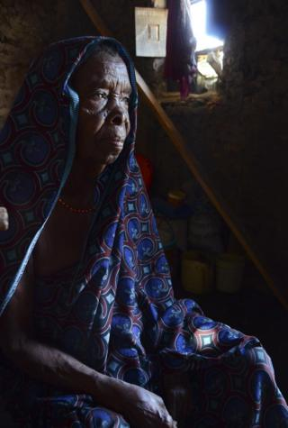 An elderly woman in a headscarf.