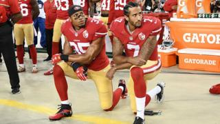 Colin Kaepernick (right) kneels during the Star Spangled Banner