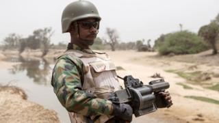 Nigerian soldier wey carry grenade launcher tanda for di Yobe river wey separate Nigeria from Niger Republic, Damasak town for North East, as thousands of people wey dem free from Boko Haram dey go back to dia house.