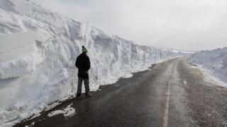 A man stands beneath a huge snow drift on a road in the Pennines on March 20, 2018 in Allenheads, England