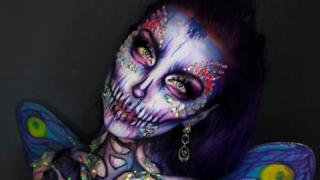 Ellie transforms herself into a fairy of death merging the aspects of a violet and pink skull and a pale blue butterfly