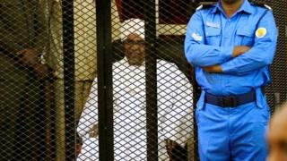 Former president of Sudan Omar al-Bashir, sitting in a cage during his sentencing