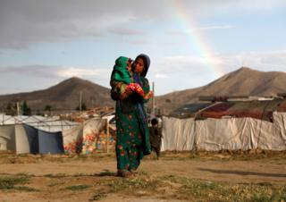 A displaced Afghan girl carries a child near their shelter at a refugee camp