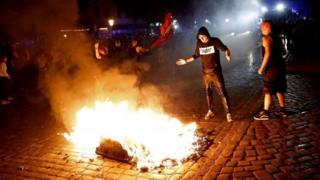 ごみに火をつけるデモ参加者(5日、ハンブルク)