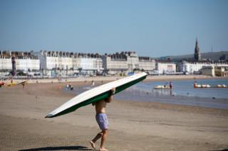 A man carries a paddle board down to the sea at Weymouth seafront in Dorset, England