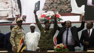 """Protest leader Ahmed al-Rabie (2nd-R) alongside Lt-Gen Abdel Fattah Abdelrahman Burhan (C), head of Sudan's ruling Transitional Military Council during the signing ceremony in Khartoum on August 17, 2019, accompanied by General Hamdan Daglo """"Hemeti"""" (2nd-L), TMC deputy chief and commander of the Rapid Support Forces paramilitaries, Ethiopian Prime Minister Abiy Ahmed (L), and Chadian President Idriss Deby (3rd-L)"""