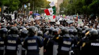 Protesters face a line of riot police in Mexico City