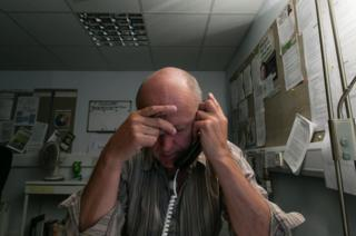 A Samaritans volunteer listens with his head in his hands.