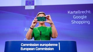 La comisionada de la UE para la competencia, Margrethe Vestager, toma una foto con su celular durante una rueda de prensa.