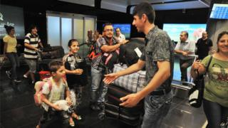 A picture taken on August 13, 2012 shows Armenian man (L) as he meets his relatives upon their arrival from Syria at Zvarnots airport outside Yerevan.