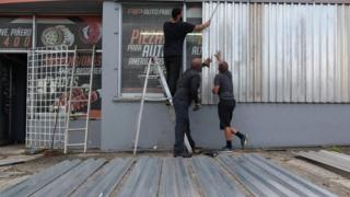 Men cover the windows of a car parts store in preparation for Hurricane Irma in San Juan