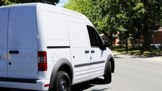 A stock image shows a stereotypical white van turning a corner on to a quiet residential street